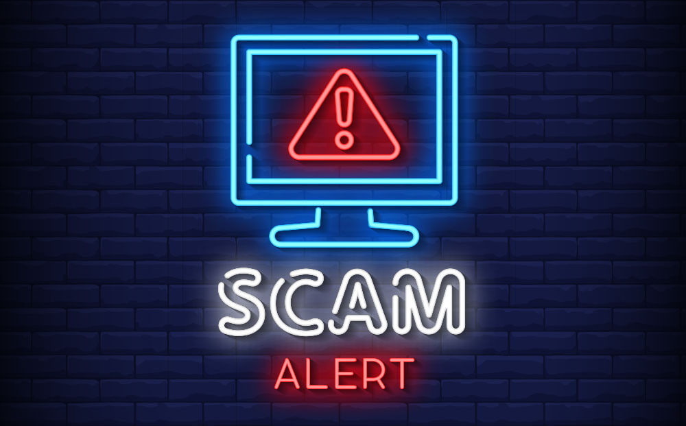 Illustration of neon lights in the shape of a computer monitor with a red error sign and the words Scam Alert written below it in neon lights